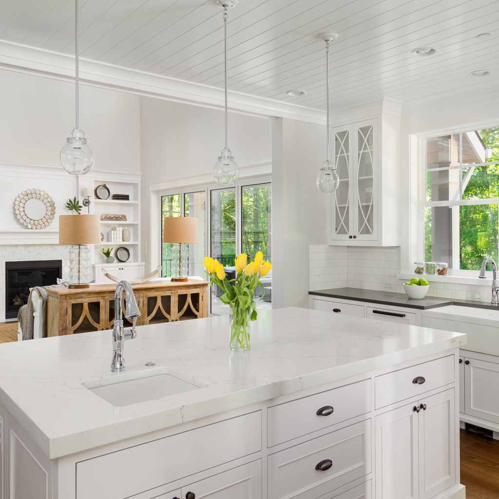 Beautiful kitchen interior with island, two sinks, hardwood floors, and view of living room with vaulted ceilings